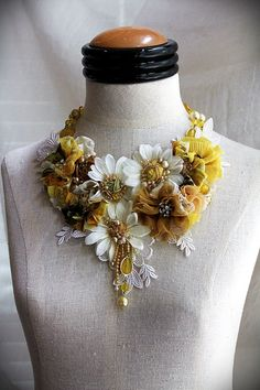SHASTA  Vintage white silk daisies are given new life repurposed as focal points in this one of a kind handmade statement necklace. Each is centered with a beaded silk fabric rosette. Printed chiffon fabric (repurposed from a 1960s blouse) are fashioned into floral elements, centered with vintage and antique rhinestone and gold filigree buttons.  Other bits of silk fabrics, in varying shades of yellow, are gathered or rolled into rosettes and embellished with vintage faux pearls, seed beads…