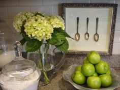 Kitchen counter top styling...frame silverware for instant art (looks like a shadow box) Group three glass vessels, two serve as canisters, and the other serves as a vase. All three vessels are paired with a ruffle edged silver tray filled with fruits of the season.