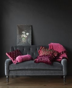 Dark living room with art. #black #walls #decoration #interior #design #room #sofa #grey #purple #pillows #pink #magenta #painting #flowers