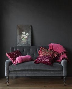 Dark living room with art. #black #walls #decoration #interior #design #room #sofa #grey #purple #pillows #pink #magenta #painting #flowers