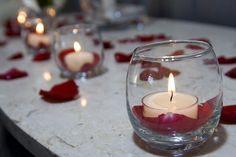 1 copo de vidro + velas no acrílico - http://www.colibrivelas.com.br/vela-lamparina-pequena-com-10-unidades.html e pétalas de rosa - Simples e bonito