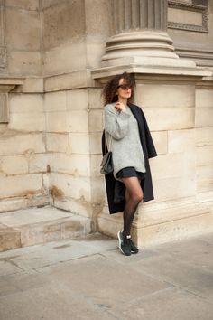 pull gris, jupe noire, collants, manteau bleu marine