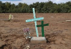 """20160929 - Crosses reading """"Hope"""" and """"Not forgotten"""" in Spanish mark an immigrant's grave in Holtville, California. Hundreds of immigrants, many who died while crossing the desert from Mexico into the United States, are buried in a pauper's cemetery. Many of the concrete grave markers simply read """"John Doe."""" # John Moore / Getty"""