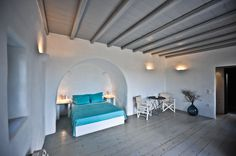 Traditional arched bedroom with build bed and night tables, wooden floor and ceiling.