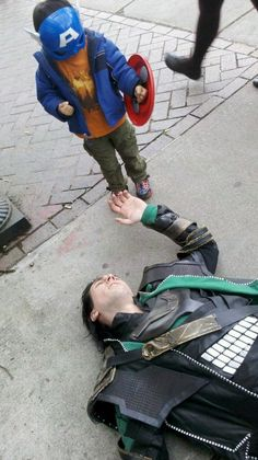 Little Captain America defeated Loki - Kid in funny Captain America costume standing over defeated Loki from The Avengers.  I am beginning to really like   Tom Hiddleston!