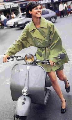 Beautiful girl in a green raincoat walking her silver Vespa scooter