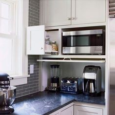 A flip-down door hides a blender, a toaster, and a coffee maker stored on this countertop. More storage is afforded by a slide out drawer next to the microwave.