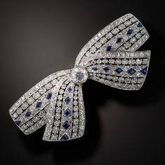 Platinum bow pin delicately pierced featuring a bezel set old European cut diamond (.40 carat, G-H color, VS clarity) with 265 diamonds (2.70 carats total weight) set in the ribbons in geometric settings with lozenge shaped sapphires dotted throughout; spectacular craftsmanship and detail. This pin measures 3/4 X 2.