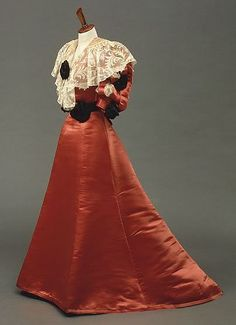 Dinner dress, House of Worth, circa 1902. Bodice and skirt of silk satin; five-panel skirt with train; bodice has handmade bobbin lace collar, machine-made tulle trim at neck, handmade tulle trim along front edge, and silk rosettes.