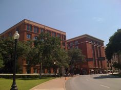 The most famous building in Dallas:  the old Texas school book depository (now home to the Dallas County Commissioners Court and the district attorney).  Lee Harvey Oswald is believed to have fired the shots that killed president John F. Kennedy from the sixth floor window.  The infamous winndow is on the top floor, the window fartherest to the right, in the first of the two similar buildings as you are looking up the hill in this photo. The trees that obscure the front of the building were ...