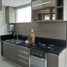 Inspiração de cozinha com bancada em granito preto, armários inferiores fendi e aéreo em vidro bronze. (Quem souber o autor favor marca-lo aqui em baixo)
