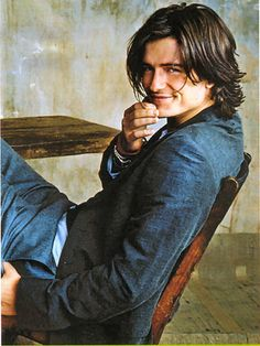 Orlando Bloom featuring his hipster wall, chair, floor and table... oh, and hair: his hair is pretty damn hipster! Hipster all over the place!