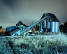 "Contemporary color photograph titled Conveyor & Silos.  Note from artist: I had to shoot this scene through the gate in a chain link fence. Notice how the metal silos seem to glow.  This 11""x14"" print is presented in a 16""x20"" white mat."