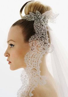 Bride's classic top bun with beautiful jeweled headpiece and lace veil