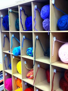 """Finally figured out a solution for yarn skeins at the weaving station that works! Found a shoe cubby at Goodwill, and attached sticky clips to inside to feed the yarn through. Kids pull one """"wingspan"""" of yarn from fingertip to fingertip from the sticky clip and snip. The yarn moves smoothly through the stickly clip and keeps it in place. No more tangles!"""