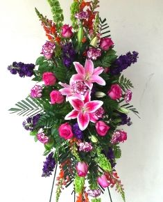 Hot pint roses, stargazer lilies, snap dragons, and purple stock this standing arrangement is beautiful.