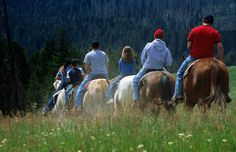 Horseback riding is an adventurous way to hit the trails in Yellowstone National Park © Carol Polich / Getty Images