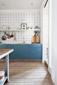 cuisine scandinave, carrelage mural blanc, placards bleus et sol en planches de bois