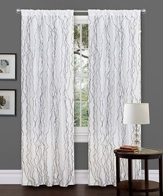 Add an element of elegance to the décor and adorn a window with this classic curtain. With white sheer voile ruffling contrasted in chic black, this luxurious treatment features a convenient built-in pocket that easily slides onto a rod for quick installation.Includes one curtain panel and one tieback42'' W x 84'' H100%...