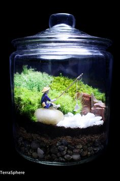 Japanese garden terrarium features a fisherman relaxing atop his river rock with a tiny white fish on his line with a realistic forest scene in the background. Terrarium features 3 different types of moss: mood, spoon and reindeer moss. White river rocks, fisherman and petrified wood pieces.  Measures 9H x 6W(with lid)  Comes fully assembled with separately packed miniatures.  Super easy to care for. No direct light, occasionally open top and spritz with included filtered water spray bottle…