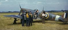 Preparing for battle: A noticeably young ground crewmen prepare a Spitfire in a field outside of London during the height of the Battle of Britain. In the foreground a group of pilots pause to discuss tactics