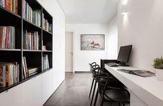 במסדרון שמחבר בין המטבח לחדרים הפרטיים תוכננו פינת עבודה ארוכה וארונות אחסון לבנים עם קובייה שחורה של מדפי ספרים. בקצה יציאה נוספת למרפסת ( צילום: אלעד גונן )