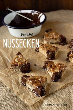 Zarter Mürbeteig und ein saftiger Belag mit karamelisierten Haselnüssen und Pekanüssen. Außerdem sind diese veganen Nussecken palmölfrei, weil sie statt mit Margarine mit Kokosfett gebacken werden. Einfaches Rezept, eifrei, laktosefrei.