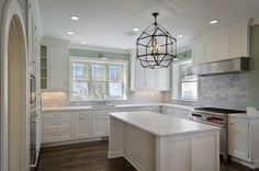 Love the white counters, dark floor, windows and backsplash. Dishwasher too far away from cabinets, though. :-)
