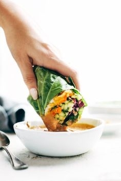 Detox Rainbow Roll-Ups dipped in peanut sauce.
