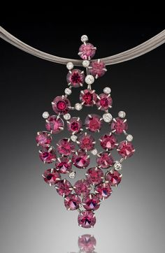 A unique pendant design by Adam Neeley.   Glam Rhodolite Garnet Pendant is bold and timeless. In this modern pendant design, an array of richly colored rhodolite garnets and diamonds are delicately set in white gold.