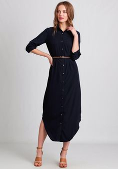 Simple and chic, this navy blue maxi dress features a button-up front with two front pockets and optional roll-tab sleeves.