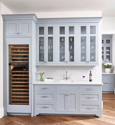 Chic butler's pantry features gray blue cabinets paired with light gray arabesque tile backsplash.