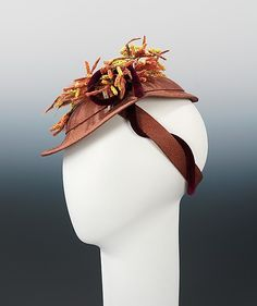 Sally Milgrim, ca. 1938.  Metropolitan Museum website description: For headwear, the late 1930s marked an era of creativity in which milliners offered unusual shapes and whimsical trimmings. For this example, milliner Sally Milgrim incorporated a bouquet of autumnal grasses and berries tied with a lush velvet cord to make the straw body appropriate for fall.