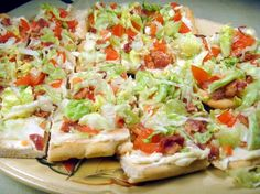 Bob's Bacon Pizza  1 Pillsbury fridge classic pizza crust  2 c iceberg lettuce  2 plum tomatoes, seeded & chopped  1 (8 ounce) cream cheese,soft  1/2 c ranch  1 garlic pressed  1/2 cup cheddar cheese, shredded  1/4 C olives, sliced  1/4 C onions, chopped   6 slices bacon, cooked & crumbled  Directions  Bake crust, Cool completely,  Combine cream cheese, 1/4 C ranch dressing & garlic.  Spread evenly over crust.  Top with lettuce, tomatoes, cheese, olives, onion, bacon  Drizzle w/ remaining…