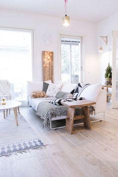 tons neutros na decoração da sala de estar, sala de estar decoração neutra, sofá brnaco com almofadas em apreto e branco, piso de madeira, mesa de centro branco, mesa lateral banco rústico