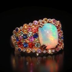 This exceptional ring features a mystical oval-shape Neopolitan Opal™ accented by sparkling white diamonds and multicolor round-shape sapphires. (Blueberry Sapphires™, Strawberry Sapphires™, Sunny Yellow Sapphires™, green sapphires, and orange sapphires.