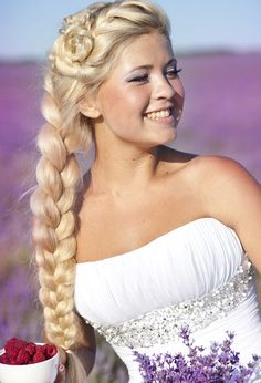 Classic wedding hairstyle with thick, long, blonde braid and rose-twist bun on top