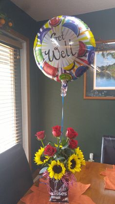 Get well flower arrangment I made for under $15! Roses and sunflowers were purchased at Wal-Mart. The vase, raffi, balloon and kisses were purchased at the dollar tree.