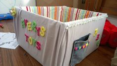 Child's DIY Toy Box. Cardboard box covered in fabric decorated with foam sticky letters (no sew, hot glue only)