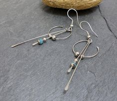 Earrings made with a stainless steel connector shaped and hammered by hand from 20 mm in diameter, two hammered stems, one bead faceted blue jade beads in steel and two steel cups. Height including hook: 7 cm. Weight of one Earring: 1.2 g. 316 L stainless steel hook. Nickel free. Also