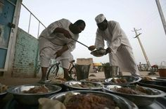 Sudanese men prepare food before an Iftar dinner by the side of the Khartoum highway in the village of al-Nuba during Ramadan