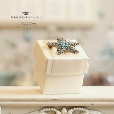 Inspired by the Jewels and Sea stationery collection, this wedding favour box features a lovelyn turquoise starfish brooch on a nest of delicate satin ribbon. per item Wedding Stationery, Wedding Invitations, Wedding Favor Boxes, Wedding Tips, Starfish, Favors, Delicate, Engagement Rings, Jewels