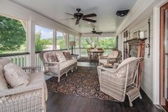 Charming wicker furniture is situated around a stylish patterned rug on this spacious screened porch. The arrangement provides the perfect spot for morning coffee or afternoon tea.