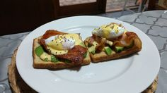 Poached eggs on bacon, avocado and toast topped with a hollandaise sauce