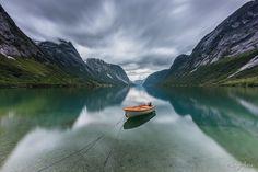 En cuanto vi esta barquita sabía que algo bueno iba a salir de aquí. Paré al ver el lago y enseguida me puse a hacer fotos. Esta es una larga exposición, pero tengo de todos los tipos. La suerte fue que apenas se movió la barca durante la exposición. Hay que hacer mucho zoom para notarlo.   ¿Y aquí que tiempo utilicé?  #longexposure #norway #lake #boat #mountain #fjords #clouds #movement #reflection #symmetry #landscape #nature #earth #nd_filter #firecrest #formatthitech @formatthitech…
