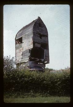 Telham Hill post mill, near Hastings,East Sussex,c 1960s. This large Sussex post mill, similar to Cross in Hand and Windmill Hill post mills,and probably built by Medhurst of Lewes, was built in 1747 and ceased working in the First World War when the sails were taken down. It was used for many years to advertise the 'Ye Olde Mill tea room' before falling into disrepair and finally being demolished in 1982.