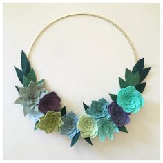 SUCCULENT FELT FLOWER WREATH // Handmade of wool blend felt with a 2 week turnaround time. This modern beauty is a fun take on a felt flower wreath. Wreath comes on a gold hoop base and features ten handmade felt succulents in shades of sage, ice blue, fern, violet, dusty purple, julep, seafoam, pistachio, rainstorm and blue spruce. Finished with meadow green and evergreen leaves. Wreath measures 14 inches at its widest. To protect the vibrant colors, we suggest that you hang this ...