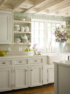 Cottage-style kitchen with whitewashed wood, bright white tiles and sage green-painted paneled walls and kitchen island.