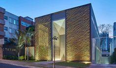 Um trançado de bambu feito artesanalmente compõe as folhas da porta de correr da fachada da loja Tetum, em Belo Horizonte. Cada uma delas mede quatro metros de largura por dez de altura, gerando o desafio para a produção da caixilharia de alumínio e o uso de roldanas especiais, com 120 milímetros de diâmetro, em aço inox.