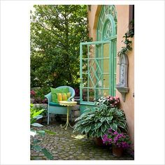 Turquoise wicker chair and yellow bistro table on paved patio with plants in terracotta pots next to classical styled glass door - Hosta, Ilex aquifolium, Impatiens and Oxalis